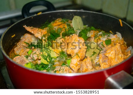 Meat with onions, carrots, dill and Bay leaf is stewed in a saucepan. Home cooking. #1553828951