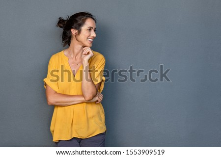 Mature beautiful latin woman isolated on grey background looking on side with copy space. Portrait of positive latin woman smiling. Happy middle aged lady standing against grey wall and thinking. #1553909519