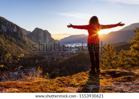 Adventurous Girl Hiking in the mountains during a sunny Autumn Sunset. Taken Squamish, North of Vancouver, British Columbia, Canada. Concept: Adventure, freedom, lifestyle #1553930621