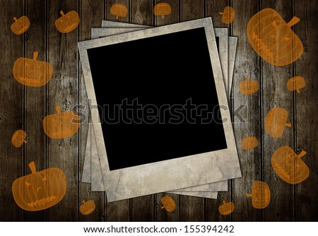 Retro photo frames on brown wooden background with pumpkins