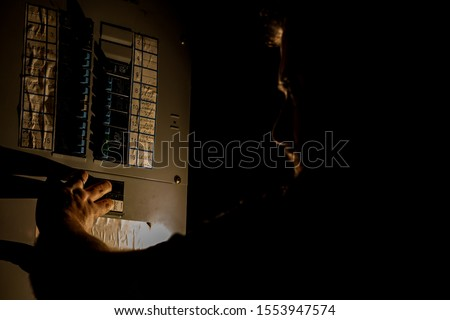 A man, visible only as a faint silhouette, is using a flashlight to investigate a home fuse box in his basement during a power outage. Royalty-Free Stock Photo #1553947574