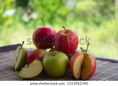 The red apples and the green apples are placed on the table, the background is a hazy lawn. #1553962340