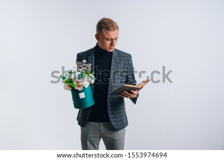 "A young guy in the image of a teacher holds a box of flowers. Translation of the text on the wooden plate ""Happy Teacher's Day."""
