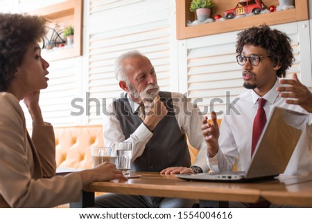A young man explaining in details his new business model to two investors. The investors carefully listen to what he has to say. #1554004616