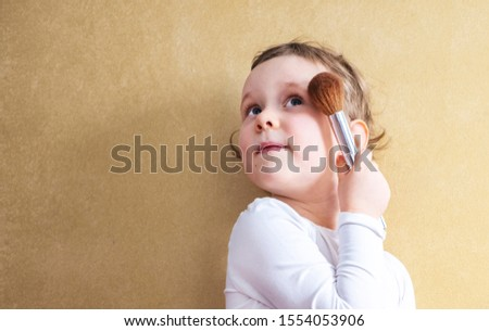 The child, a little girl of 4 years old, does makeup, imitates adults. A blonde with short hair in a white T-shirt holds a makeup brush in her hand. Orange wall and place to feast #1554053906