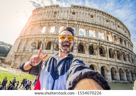 Happy tourist taking a selfie at the Colosseum in Rome