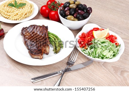 meat table : rare medium roast beef fillet and pasta with tomatoes asparagus and several kinds of olives, served on white dish over light wood #155407256