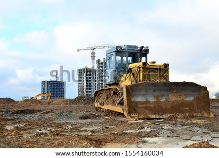 Bulldozer during of large construction jobs at building site. Land clearing, grading, pool excavation, utility trenching and foundation digging. Crawler tractor,  dozer, earth-moving equipment.  #1554160034