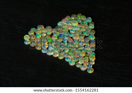 Opals gemstone from Ethiopia lies on black background. White fire opals with rainbowlike fire. Natural fire Ethiopian opal, small stones to create jewelry. Handmade stone jewelry. Love, Heart stones.