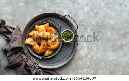 Latin American fried empanadas with  sauce. Top view.                              #1554184889