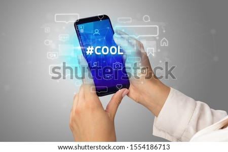 Female hand typing on smartphone with #COOL inscription, social media concept #1554186713