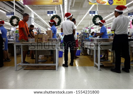 PASIG CITY, PHILIPPINES – NOVEMBER 3, 2019: Employees of a grocery store serve customers at the cashier or check out counter. #1554231800