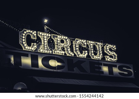 Spooky old dimly lit circus sign with light bulbs in the dark over a ticket stand in black and white. Typical view of an entrance to a circus. Concept of madness and scary. #1554244142