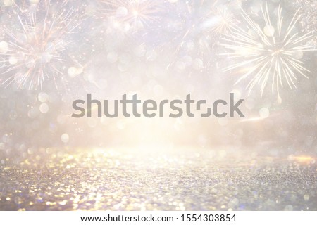 abstract gold and silver glitter background with fireworks. christmas eve, 4th of july holiday concept #1554303854