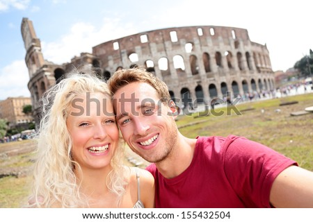 Tourist couple in Rome taking self-portrait photo by Coliseum. Happy young tourists traveling in Italy. Beautiful blonde woman and man in their 20s on holidays vacation in Europe.