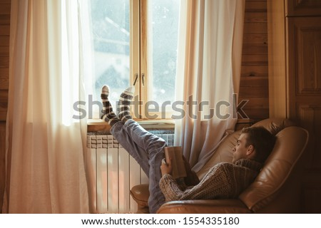 Young man in warm sweater reading book while relaxing on armchair by the window and electric radiator inside cozy log cabin #1554335180