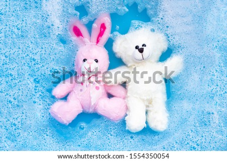 Soak rabbit doll with  toy teddy bear in laundry detergent water dissolution before washing.  Laundry concept, Top view #1554350054