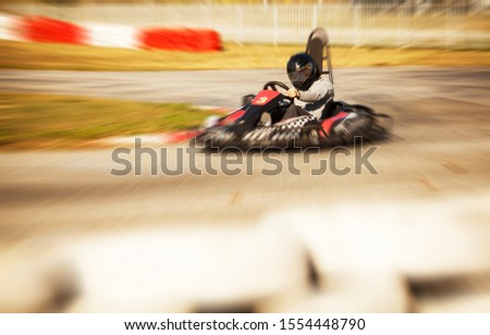 Go kart driver racing on the track, speed and adrenaline, zoom burst photo effect #1554448790