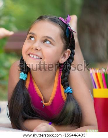 Portrait of pretty hispanic girl lying on grass in summer day