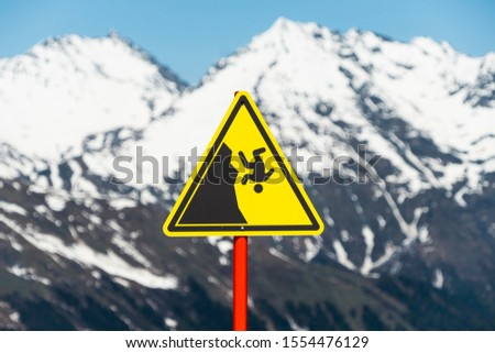 Yellow danger sign in the mountains. Hiking Safety Warning.