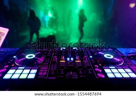 DJ mixer in the booth on the background of the dance floor with dancing people Royalty-Free Stock Photo #1554487694