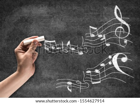 Businessman hand with chalk draws music notes sketch on chalkboard. Freehand white chalk illustration on blackboard. Music art school advertisement. Musician or composer writing music notes.