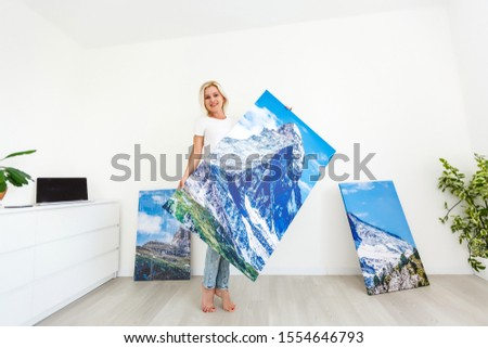 woman with a picture stands near the wall
