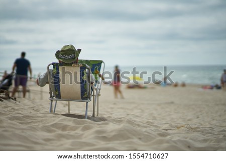 Resting man at the beach. Man relaxing at the beach     Royalty-Free Stock Photo #1554710627