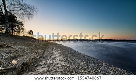 Sunset at the river coast. Smooth water at river Royalty-Free Stock Photo #1554740867