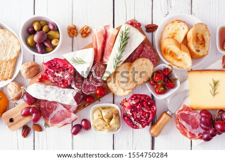 Charcuterie board of assorted cheeses, meats and appetizers. Above view table scene on a white wood background. #1554750284