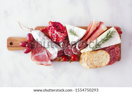 Serving board of assorted meats, cheeses and appetizers. Top view on a white marble background. #1554750293