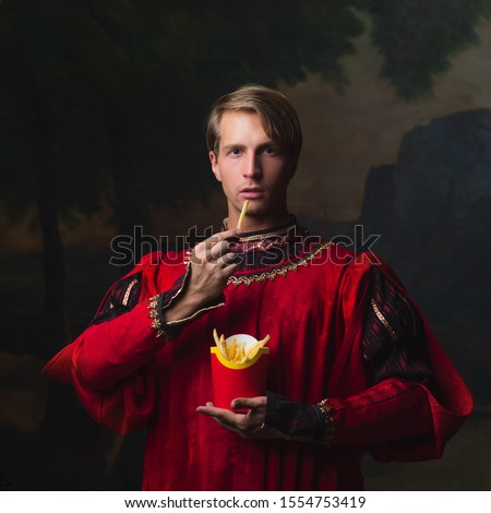 handsome man in a Royal red doublet eating French fries, red box of fries. funny duet of medieval style and modern attributes, concept.