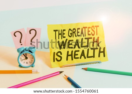 Text sign showing The Greatest Wealth Is Health. Conceptual photo Many sacrifice their money just to be healthy Mini size alarm clock beside stationary placed tilted on pastel backdrop. #1554760061