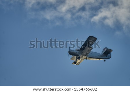 British old aircraft flying above Riga. airplane biplane with piston engine and propeller. Royalty-Free Stock Photo #1554765602