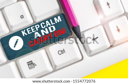 Conceptual hand writing showing Keep Calm And Carry On. Business photo text slogan calling for persistence face of challenge White pc keyboard with note paper above the white background.