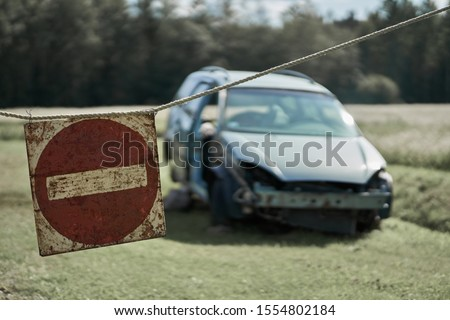 Damaged car and stop sign at one shot Royalty-Free Stock Photo #1554802184
