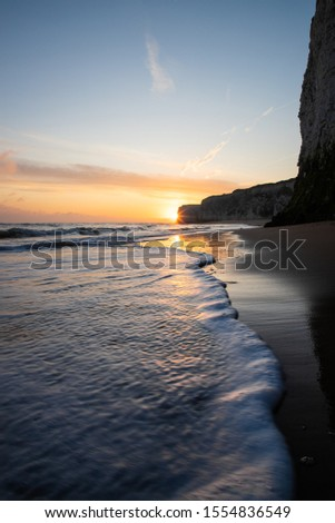 Waves lapping at the shoreline during a golden sunrise at the beach - Botany Bay  #1554836549