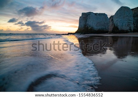 Waves lapping at the shoreline during a golden sunrise at the beach - Botany Bay  #1554836552
