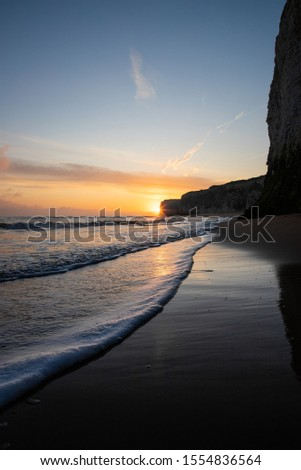Waves lapping at the shoreline during a golden sunrise at the beach - Botany Bay  #1554836564