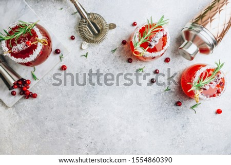 Christmas cranberry cocktail in glasses decorated with coconut on light gray festive background with fir branches, fresh berries and rosemary. Holiday concept. Top view. Flat lay #1554860390