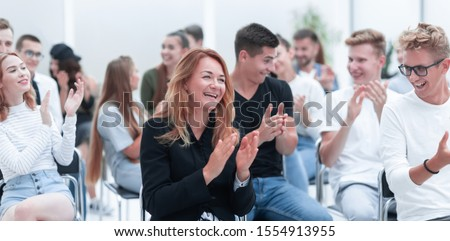 close up. smiling young woman applauding sitting in conference room Royalty-Free Stock Photo #1554913955