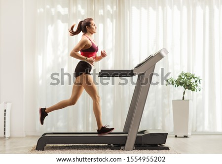 Full length profile shot of a young woman running on a treadmill at home #1554955202