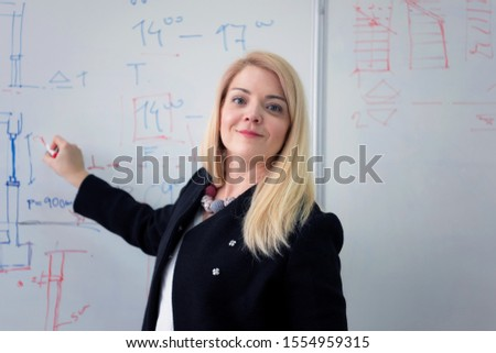 Female Architecture teacher at work. Female professor explain architectural projects to students. Beautiful female university architecture professor smiling into camera. #1554959315
