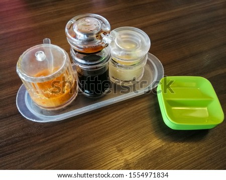 Three sauces for Hainese Chicken Rice, Chilli sauce, Soy sauce and garlic ginger sauce were prepare on top of wood table. Green sauce plate also put together with sauces.  #1554971834