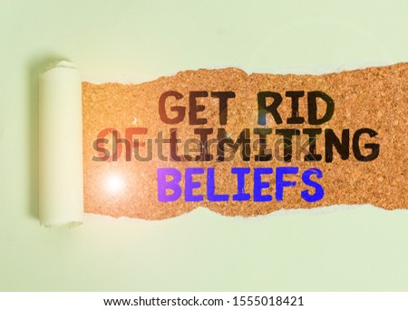 Writing note showing Get Rid Of Limiting Beliefs. Business photo showcasing remove negative beliefs and think positively Cardboard which is torn placed above a wooden classic table. #1555018421