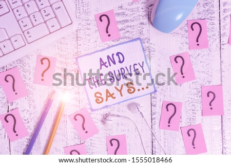 Writing note showing And The Survey Says. Business photo showcasing doing poll and bring the results discuss with others Writing tools and scribbled paper on top of the wooden table. #1555018466
