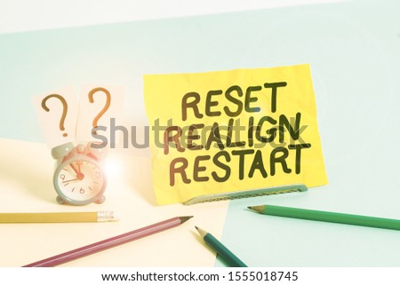 Text sign showing Reset Realign Restart. Conceptual photo Life audit will help you put things in perspectives Mini size alarm clock beside stationary placed tilted on pastel backdrop. #1555018745