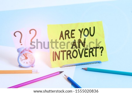 Text sign showing Are You An Introvertquestion. Conceptual photo demonstrating who tends to turn inward mentally Mini size alarm clock beside stationary placed tilted on pastel backdrop. #1555020836