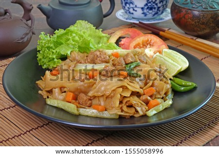 Stir fried flat noodle with black soy sauce, tofu, carrots and green vegetables. Vegetarian food for vegetarian festival. Thai style stir fry flat noodle. (Pad See Ew) #1555058996