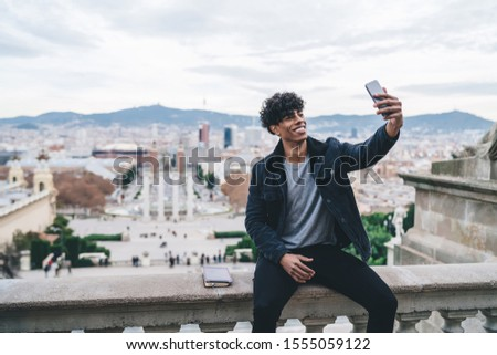 Happy cheerful Latino male traveller dressed in stylish outfit resting during Spanish vacations to Barcelona city clicking selfie pictures on Montjuic area, millennial man photographing himself